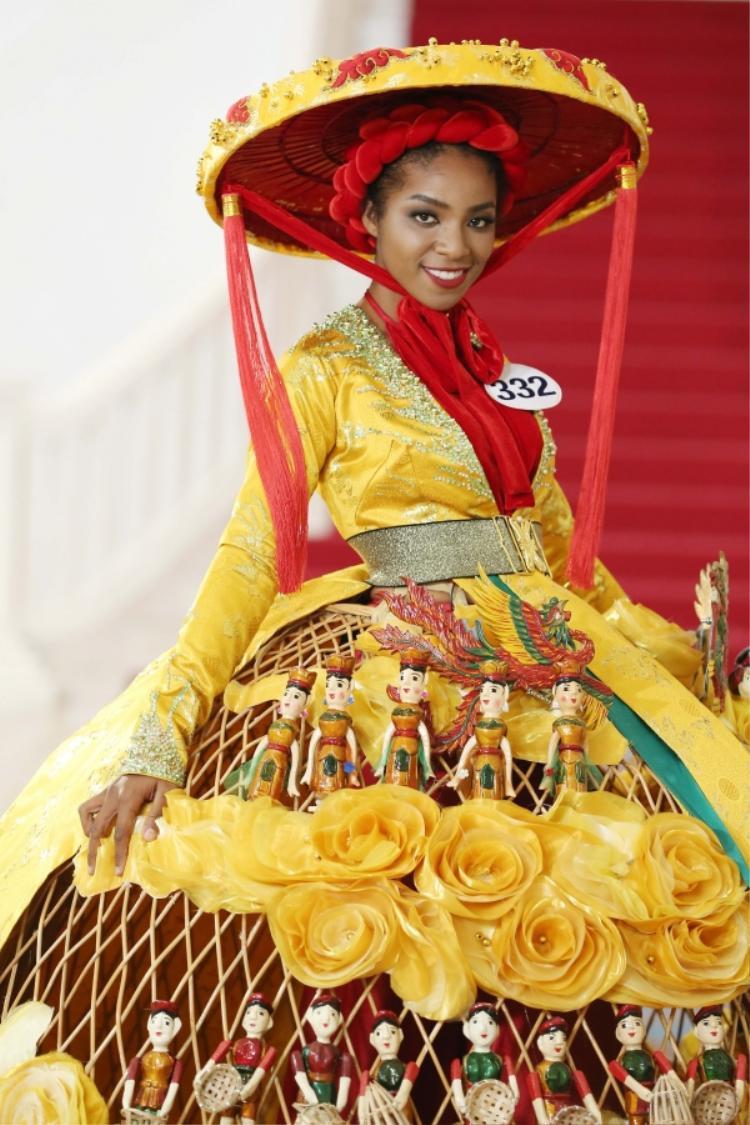 Là thí sinh mở đầu, Huỳnh Tiên diện bộ trang phục lấy cảm hứng từ nghệ thuật múa rối nước cổ truyền. Áo tứ thân, gam màu vàng cùng chất liệu gấm khiến bộ trang phục toát lên nét truyền thống đặc trưng.Không thể phủ nhận tuy mang vẻ đẹp lai, nhưng Huỳnh Tiên thật sự tỏa sáng trong bộ quốc phục này.