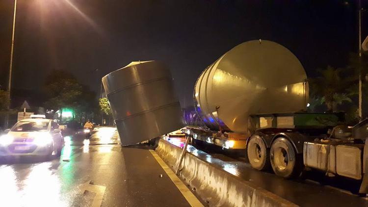 Xe tải chở hai bồn lớn lao vào dải phân cách ngoài cùng, một chiếc bồn rơi khỏi xe.