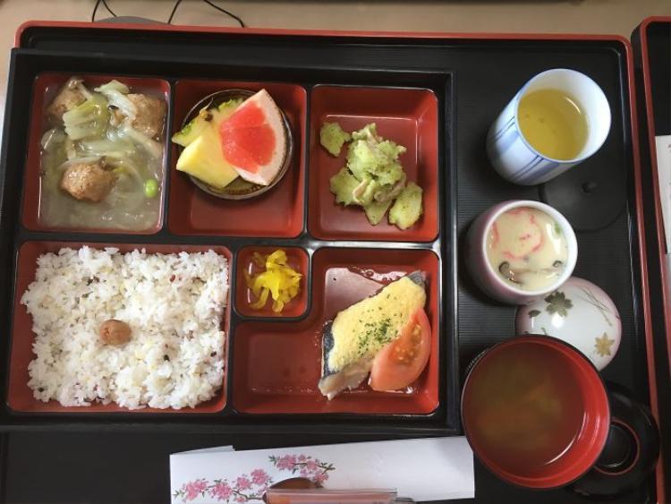 Thịt gà, cá, cơm trắng, trứng hấp, củ cải trắng, súp, trà xanh, hoa quả được trình bày đẹp mắt trong một khay nhỏ nhiều ngắn.