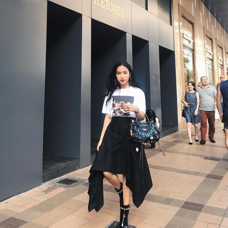 """Tham dự show Louis Vuitton tại Hong Kong, Châu Bùi không làm người hâm mộ thất vọng với danh xưng fashionista. Chân váy cấu trúc bất đối xứng đang """"làm mưa làm gió"""" khắp các sàn diễn thời trang phối ăn nhập áo phông họa tiết basic. Boots và túi xách Balenciaga hoàn thiện tổng thể."""