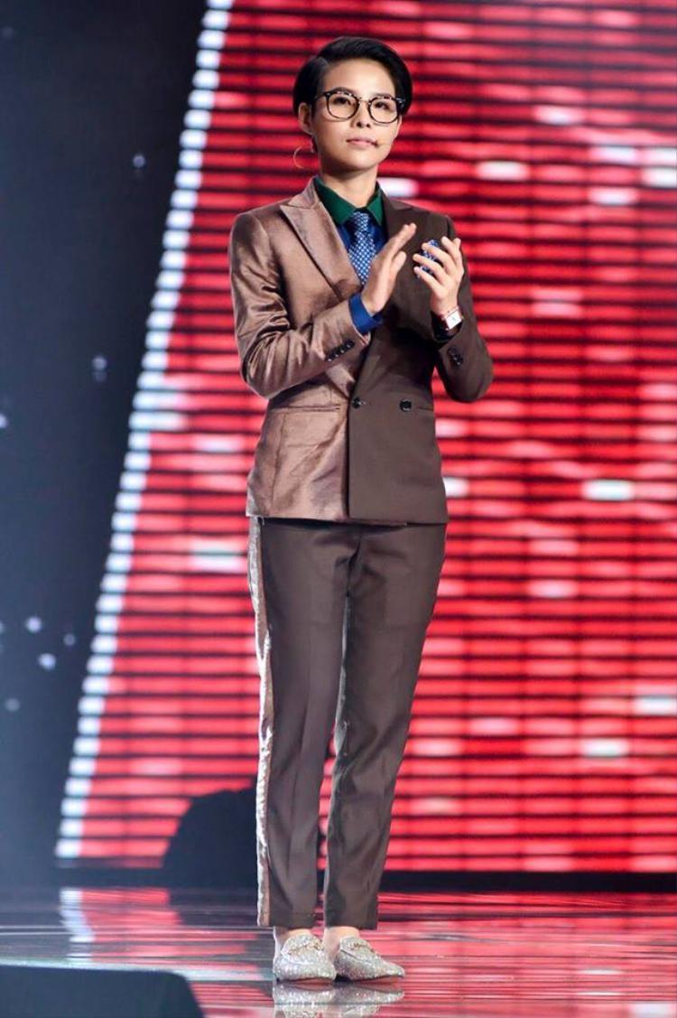 Theo phong cách men's wear đặc trưng, Vũ Cát Tường cá tính và mạnh mẽ với cây vest gam màu trầm. Cách phối hợp chất liệu lạ mắt cùng điểm nhấn cravat chấm bi đi kèm giày lấp lánh khá thú vị. Tổng thể mới lạ đem đến cho huấn luyện viên Giọng hát Việt nhí 2017 cái nhìn thu hút.