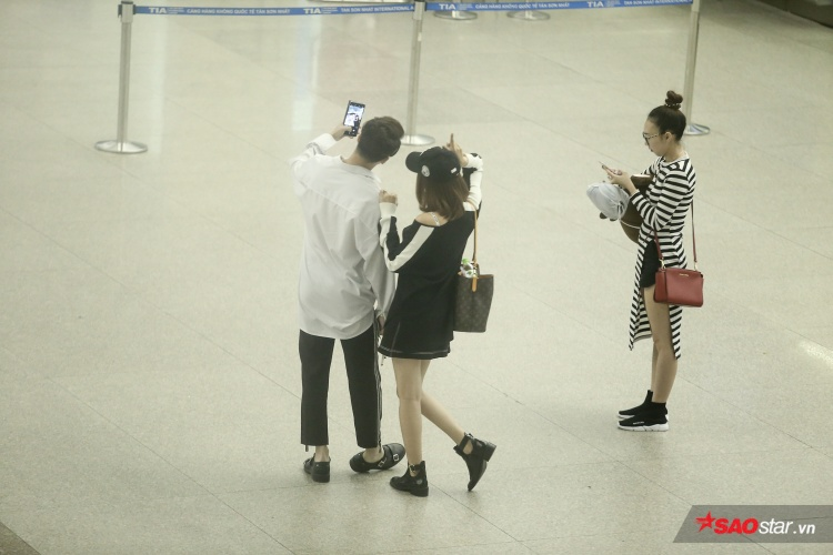 Cặp đôi thân thiết, chụp ảnh selfie giữa sân bay.