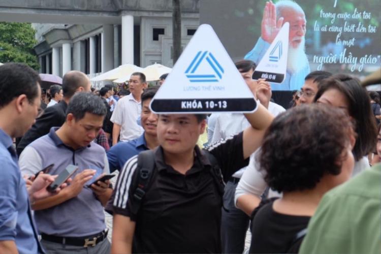 Cựu học sinh mang theo ảnh biểu tượng của trường có ghi niên khóa đến dự lễ tang.