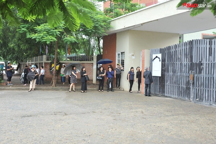 Nhiều thầy giáo lớn tuổi đứng trầm ngâm khá lâu trước tấm biển cáo phó dán trước cổng trường dù lúc này trời đã bắt đầu đổ mưa.