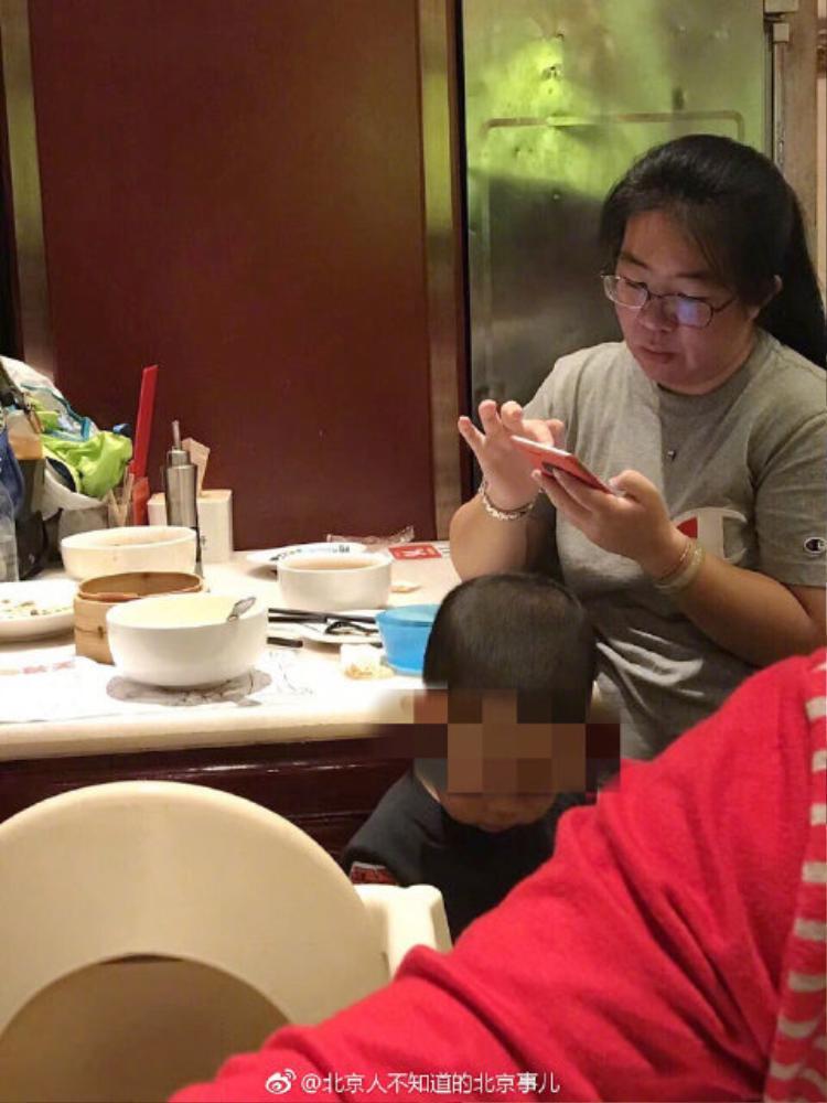 Bà mẹ thản nhiên để con đi tiểu vào bát ăn trên bàn.