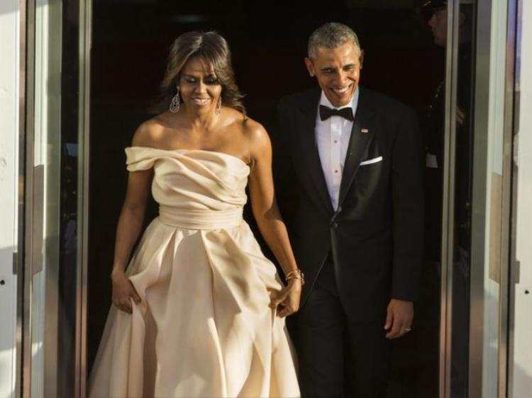 """Có thể nói, Michelle là """"quán quân"""" đầm dạ hội khi nắm trong tay hàng loạt đầm váy hàng hiệu đủ kiểu. Không cần thêm bất cứ một phụ kiện nào để tỏa sáng vì chiếc đầm Naeem Khan yêu kiều mà Michelle Obama đang diện đã quá thu hút. Kiểu tóc đơn giản, phụ kiện tay đơn giản và tỏa sáng là việc còn lại của chiếc đầm. Có thể thấy, đây là một trong những món đồ tuyệt vời nhất trong tủ đồ thời trang Michelle Obama"""