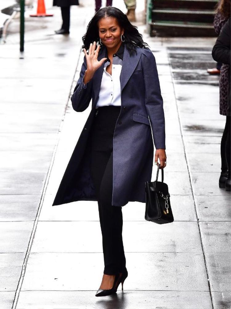 Michelle Obama chứng minh rằng việc đầu tư vào những trang phục may đo cao cấp, phù hợp với vóc dáng cơ thể không bao giờ là dư thừa. Chiếc quần âu vừa vặn, áo sơ mi lụa và áo choàng trơn màu trong bức ảnh này đã tôn lên triệt để vẻ nhã nhặn, ôn hòa của Đệ nhất Phu nhân nhưng vẫn khiến bà tỏa sáng