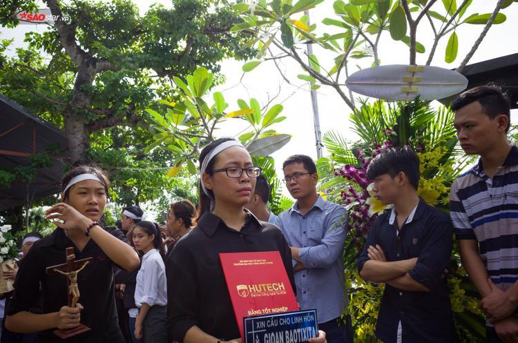 Em gái của nam sinh Nguyễn Thanh Long nghẹn ngào khi cầm di ảnh của anh trai trên tay.