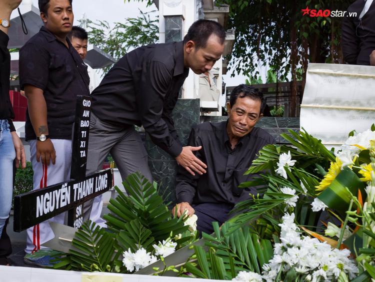 Cha của Thanh Long thẫn thờ ngồi bên mộ con trai.