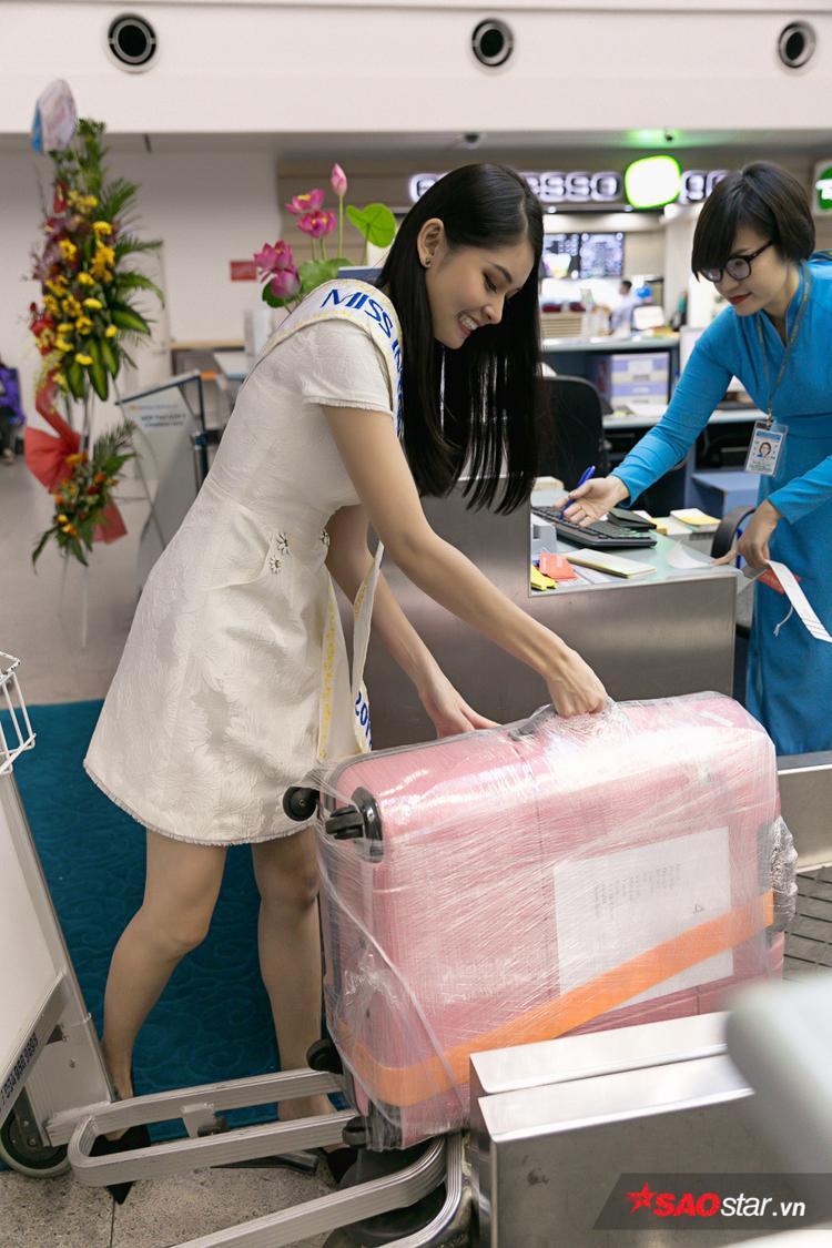 Cô khệ nệ sắp xếp hành lý để nhân viên kiểm tra.