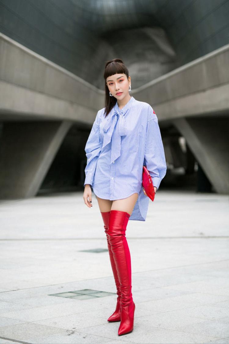 """Hoa hậu Lam Cúc diện sơ mi dáng dài phối với đôi Balenciaga đỏ rực. Đôi boots không chỉ tạo điểm nhấn cho cả set đồ mà còn """"kéo dài"""" đôi chân vốn đã vô cùng thon thả của bà mẹ một con trong lần xuất hiện đầu tiên tại Seoul Fashion Week 2017."""