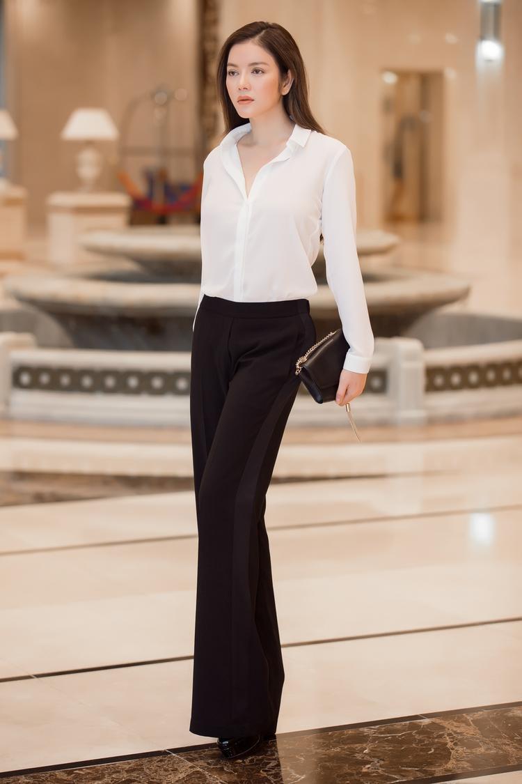 """Nữ diễn viên """"Kiều nữ và đại gia"""" toát lên thần thái, khí chất thanh lịch chỉ với sơmi lụa trắng, quần âu đen với chi tiết may phối hai bên sườn đang thịnh hành, cùng với clutch đen basic theo xu hướng minimalist. Tất cả tạo nên tổng thể sang trọng, quyền lực của vị nữ doanh nhân."""
