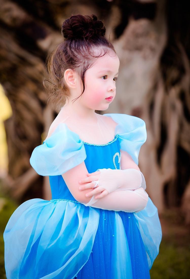 """Vì quá yêu thích nàng Lọ Lem nên """"công chúa nhỏ"""" - Cadie Mộc Trà còn xin mẹ cho diện thêm một chiếc đầm của nhân vật này trong phiên bản cổ tích, cùng gam màu xanh nhưng bộ váy này lại có thêm chi tiết hạt đính kết trái tim trên thân áo rất đáng yêu."""