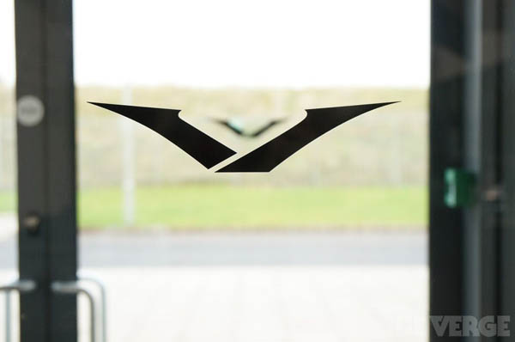 """Biểu tượng chữ V này thực tế còn ra đời trước khi cái tên Vertu được chọn. Nó thể hiện hình ảnh hai cánh tay đang mở ra khi trò chuyện của người đứng đầu mảng thiết kế Frank Nuovo. Dù vậy, logo sau đó đã được chỉnh sửa lại bởi ban đầu trông quá giống logo của Mazda. Chữ V lúc này cứng cáp hơn và vì thế cái tên Vertu đã được chọn để phù hợp với nó. Có thể bạn chưa biết, trong tiếng Latin, Vertu có nghĩa là """"những vật thể của sự tuyệt vời."""""""