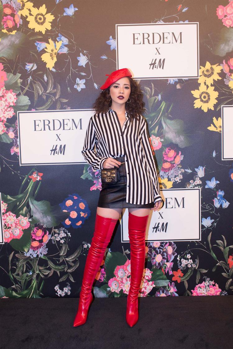 """Trước đó, Chi Pu cũng từng mắc phải lỗi tương tự khi trong sự kiện ra mắt bộ sưu tập mới của thương hiệu H&M, nữ diễn viên khiến nhiều người 'lắc đầu"""" với tạo hình như """"búp bê phiên bản lỗi"""" khi đội mũ nồi kèm mái tóc xù mì, đôi boots cao bó sát chói lóe đến nhức mắt kèm kiểu trang điểm quá đậm gây thất vọng."""