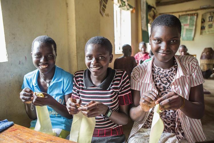 Các bé gái Uganda được dạy cách làm băng vệ sinh dùng một lần.
