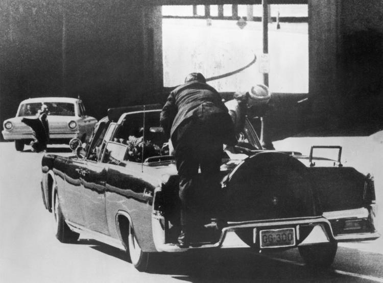 """Khi đoàn xe đi qua kho sách của thư viện Texas, tiếng """"đoàng, đoàng"""" vang lên. Ông Kennedy bị bắn trúng hai viên đạn, một ở sau lung, một viên chí mạng ở bên phải phía sau đầu. Kennedy đổ sụp về sau ghế, đệ nhất phu nhân ngả hẳn người về phía ông, còn nhân viên Mật vụ Clinton Hill nhảy hẳn lên xe. Ông Kennedy qua đời khoảng một giờ sau đó tại bệnh viện Parkland."""