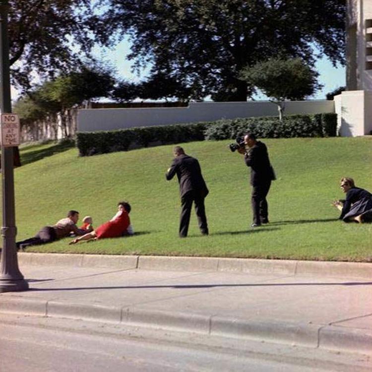 Bill và Gayle Newman, hai nhân chứng vụ ám sát, đã nhào lấy ôm hai con mình khi tiếng súng nổ. Trong khi đó, phóng viên của CBS News Tom Craven và nhiếp ảnh gia Nhà Trắng Tom Atkins giơ máy chụp ảnh.