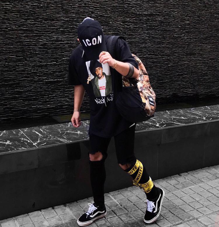 Dây bản to Off-white vắt hờ hững ngay chân trở thành điểm nhấn đầy thú vị và bắt mắt cho set đồ đen trắng của anh chàng này.