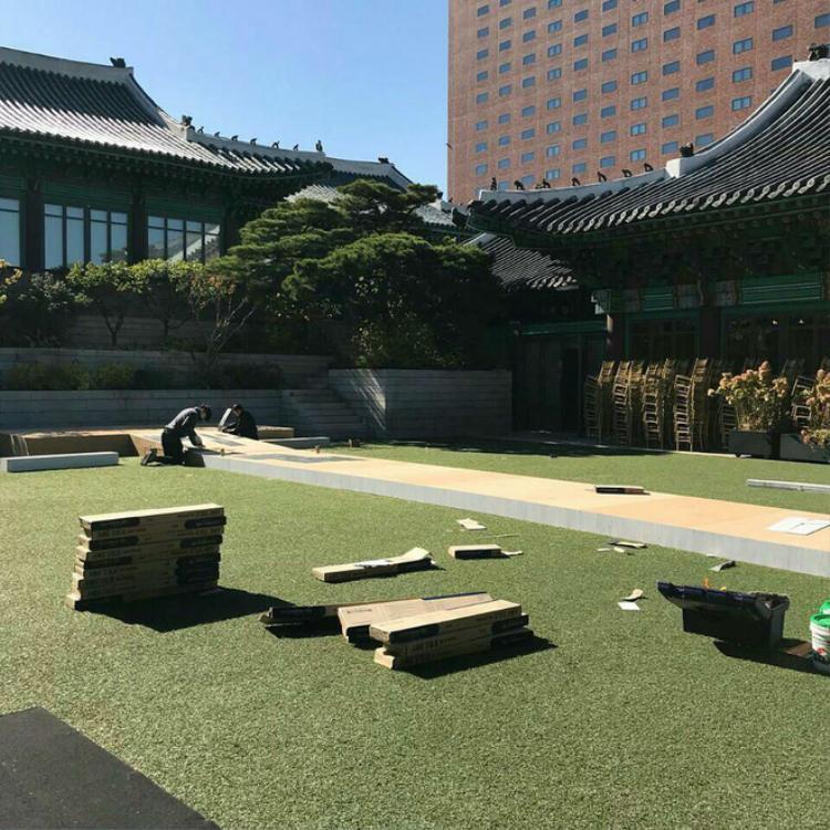 Có thể thấy các công nhân đang ghép các tấm ván gỗ trên mặt cỏ để tạo thành lối đi lên sân khấu.