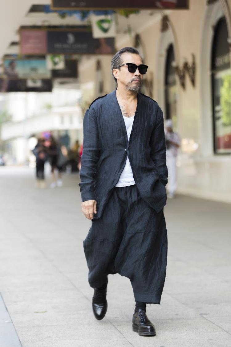 Người đàn ông hơn 60 tuổi không ai khác chính là nhà thiết kế, stylist Thuận Nguyễn. Thuận Nguyễn phong độ với suit quen thuộc nhưng lại được phối cùng chiếc quần phá cách chất lừ.