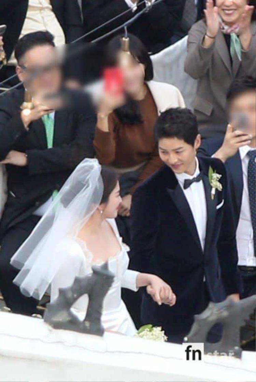 Cặp đôi nắm chặt tay, cười hạnh phúc trước mặt quan khách.