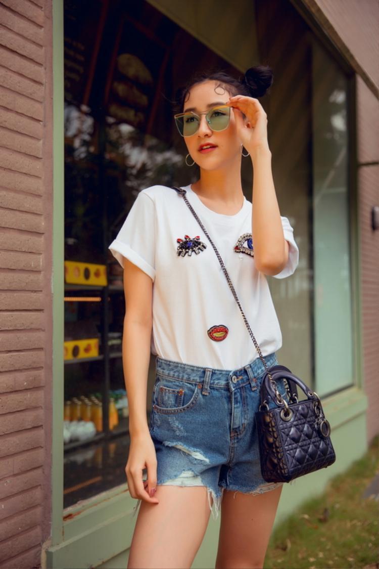 Biến hóa từ quý cô thanh lịch thành cô nàng năng động, trẻ trung, á hậu phối áo phông với denim shorts.