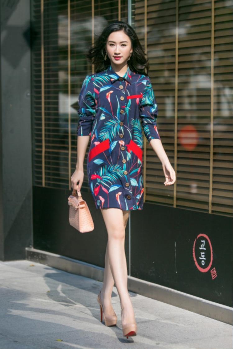 Shirt-dress họa tiết sặc sỡ, cô nàng chọn phụ kiện tối thiểu là túi cầm tay và giày cao gót cùng tông màu cũng cho ra đời một phong cách hết sức thanh lịch.