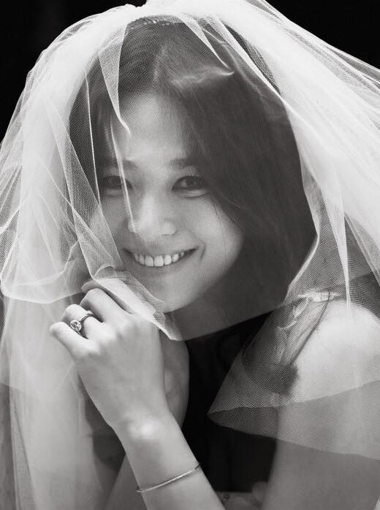 Nữ diễn viên mỉm cười hạnh phúc ngọt ngào sau tấm voan cưới. Trên tay là chiếc nhẫn đính hôn kim cương lớn.