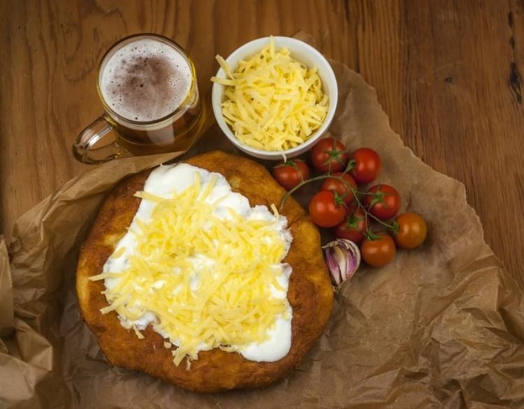 Lángos, Hungary: Bánh mì dẹp chiên phủ kem chua và phô mai tan chảy phía trên.