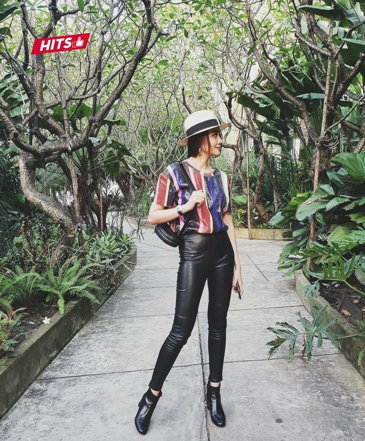 """Giống với bạn thân, Thanh Hằng cũng khéo khoe đôi chân dài bất tận trong chiếc quần legging ôm chất liệu da. """"Mẹ chồng"""" còn hoàn thiện outfit với áo freesize line sọc màu sắc, boots đen và mũ cói."""