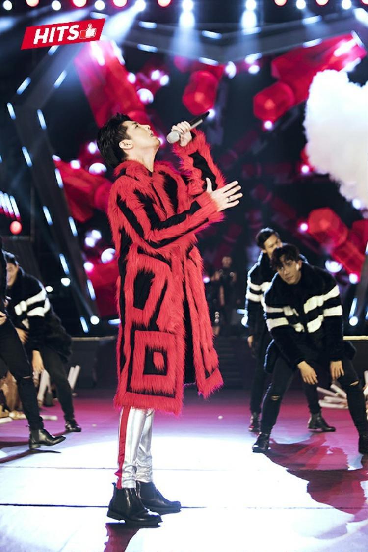 Noo Phước Thịnh cũng lựa chọn áo khoác dáng dài lông, họa tiết đỏ đen để cháy hết mình trên sân khấu. Nam ca sĩ thể hiện sự tinh tế trong gout thẩm mỹ khi quyết định phối kèm quần skinny ánh bạc, chi tiết line đỏ chạy dọc bên sườn giúp tăng chiều cao đáng kể.