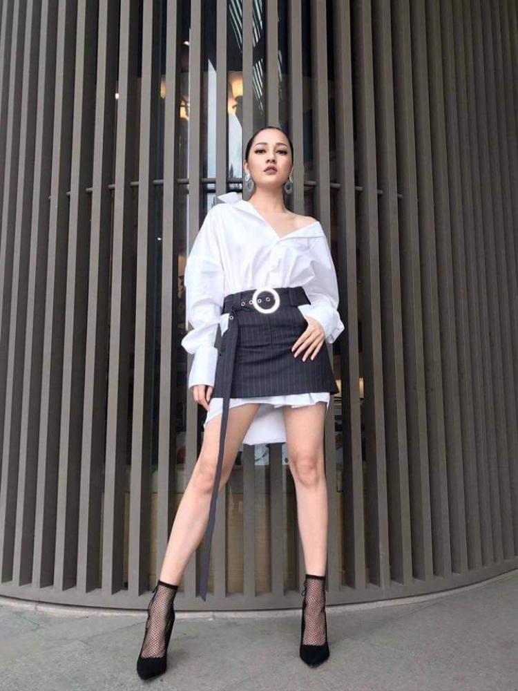 Cũng là sơmi trắng nhưng nữ ca sĩ lại phối chân váy sọc dọc, dây lưng dáng dài tạo điểm nhấn lạ mắt. Đặc biệt, chi tiết vai áo kéo trễ một bên bất đối xứng góp phần làm cho tổng thể trở nên thú vị.