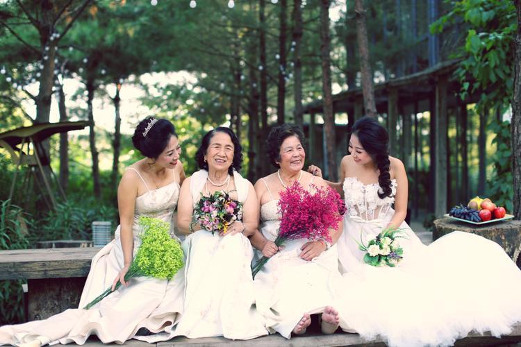 Cô dâu mặc áo cưới chụp ảnh cùng bà ngoại và hai người mẹ.