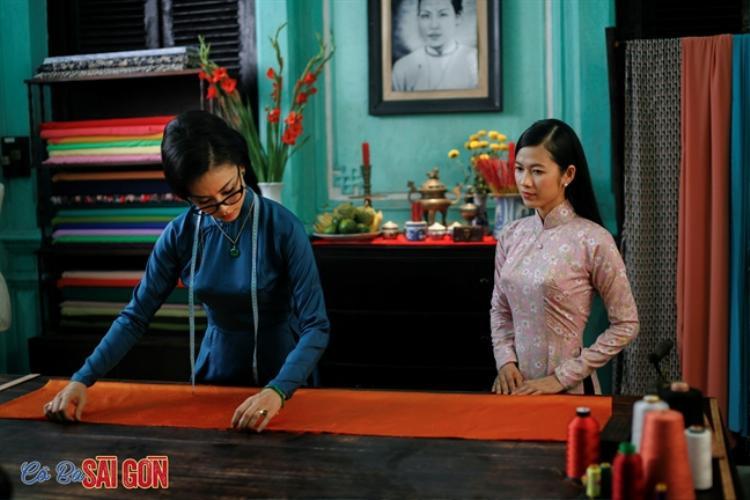 Áo dài với tông màu trầm, điểm hoa nhỏ xinh xắn được Oanh Kiều trong vai Thanh Loan hiền dịu thục nữ thường xuyên mặc trong phim.