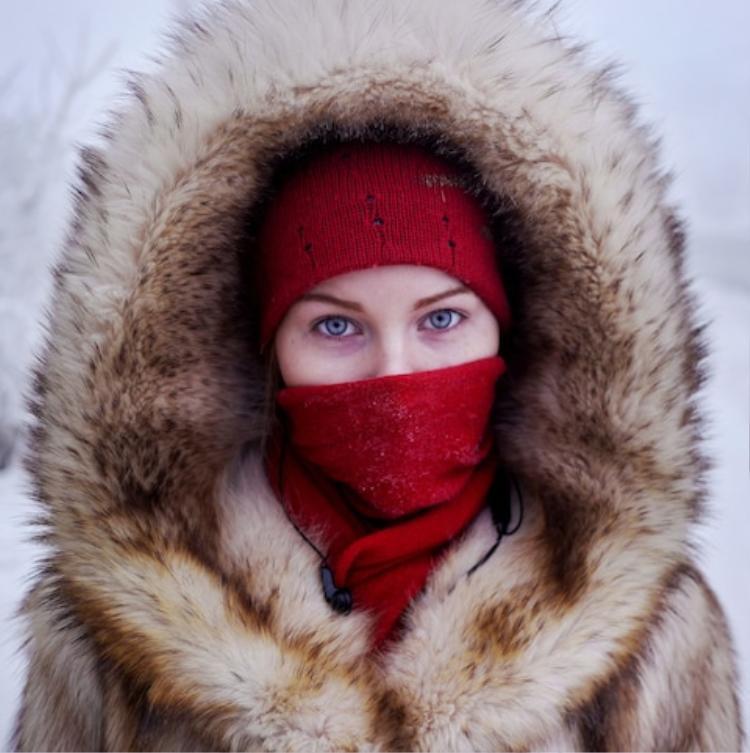 Một cô bé học sinh đang đợi xe buýt trong thành phố, nhiệt độ trong tháng một thường dao động từ -28°C đến -38°C