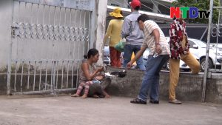 Người phụ nữ bế đứa trẻ ngồi xin tiền trước công bãi giữ xe của bệnh viện.
