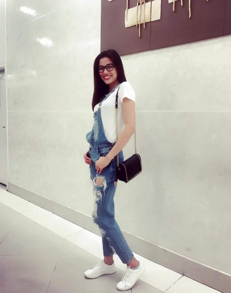 Năng động tuyệt đối với set đồ gồm quần yếm jeans rách, áo thun trắng và túi xách basic.