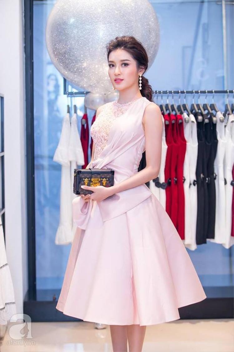Với chiếc đầm màu hồng pastel nhã nhặn này, Huyền My cũng sử dụng phụ kiện là chiếc túi Louis Vuitton Petite Malle. Lần này, cô nàng tỏ ra tinh tế khi bỏ đi phần quai túi và biến nó thành chiếc túi cầm tay sang chảnh rất hợp với bộ đầm.