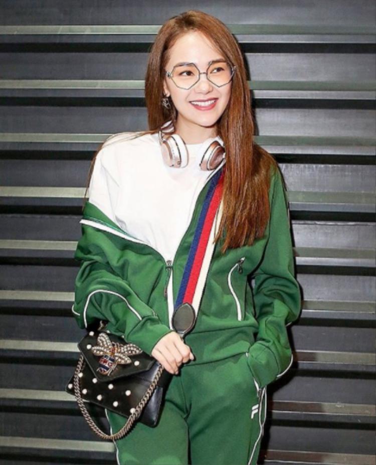 Với bộ đồ Fila màu xanh lá cây nổi bật, Minh Hằng sử dụng phụ kiện là túi Gucci và chiếc kính cô đang rất ưa thích hiện nay.