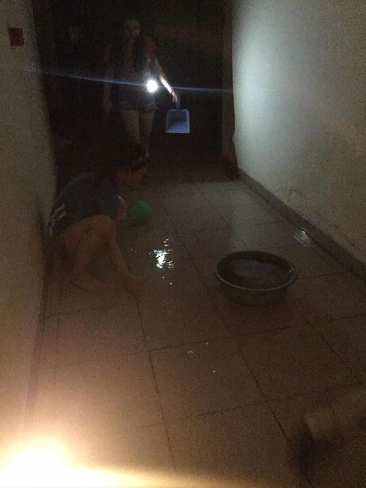 Nước mưa tạt vào hành lang các tòa nhà khiến các phòng bị ngập. KTX cắt điện nên các bạn sinh viên phải soi đèn để lau dọn.