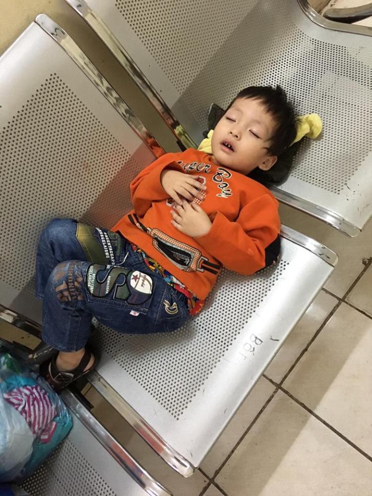 Cháu bé mệt ngủ thiếp đi trên ghế.