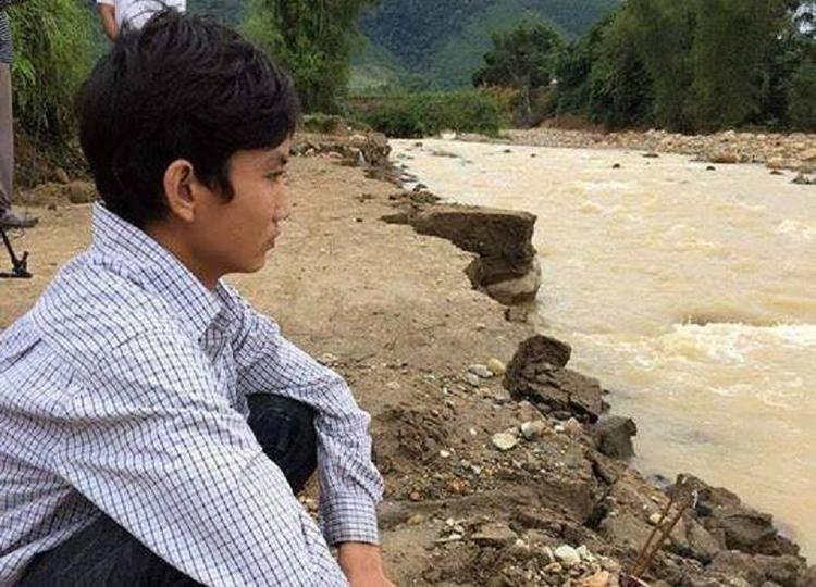 Anh Vinh thẫn thờ bên dòng nước lũ sau khi cả gia đình bị cuốn trôi.