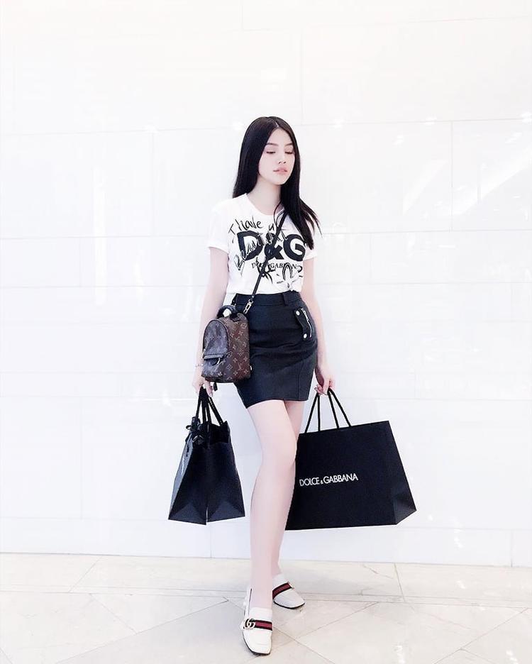 """Jolie Nguyễn năng động khi shopping trên phố với bộ cánh bao gồm áo phông D&G phối cùng chân váy ôm. """"Hoa hậu đồ hiệu"""" tiếp tục chứng tỏ đẳng cấp khi sử dụng loạt phụ kiện nhỏ xinh gồm giày và túi đeo chéo đến từ thương hiệu Gucci."""