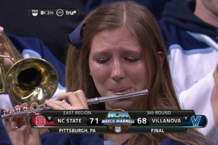 """Meme có tên """"Crying Piccolo Girl"""" này không quá nổi tiếng với người dùng Internet Việt Nam nhưng thực tế lại khá phổ biến trên thế giới. Nó được ghi lại trong một trận bóng rổ NCAA Tournament và Villanova là đội thua trận. Có lẽ đây là lý do khiến cô gái này vừa thổi sáo vừa rơi nước mắt."""