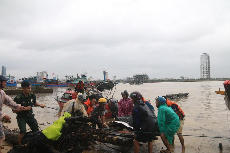 Lực lượng chức năng đưa thi thể nạn nhân vào bờ.