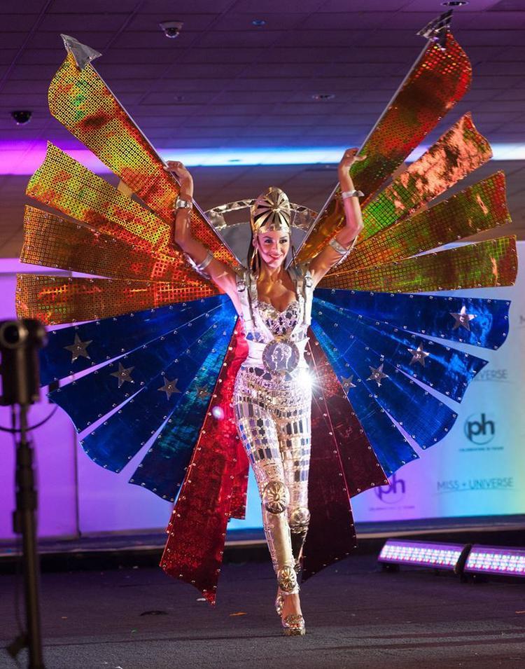 Keysi Sayago đến từ Venezuela khoác lên mình bộ quốc phục được xem không quá lộng lẫy, cầu kỳ, song gây ấn tượng với phong thái quyền lực với bộ cánh đầy màu sắc cộng hưởng với ánh sáng sân khấu giúp bộ quốc phục thêm phần lung linh.
