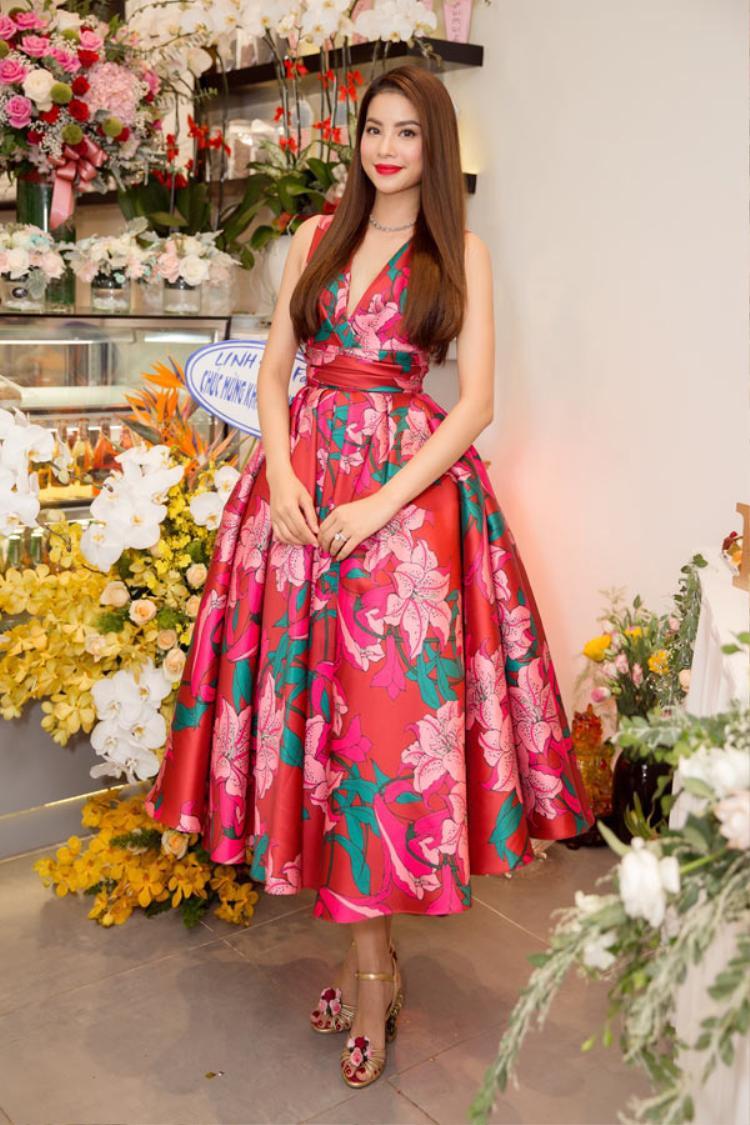 Thỉnh thoảng cô chọn cho mình những chiếc váy dáng xòe dễ di chuyển trong những sự kiện mang tính tương tác nhiều. Sự thay đổi này giúp HLV The Look đẹp mặn mà. Trong hình, người đẹp kết hợp đầm hoa màu hồng cam với giày cao gót ánh kim nhẹ nhàng, lãng mạn.