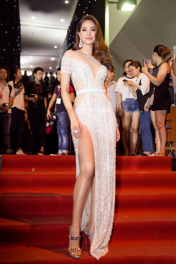 """Dù xuất hiện ở bất cứ nơi đâu """"hoa hậu quốc dân"""" luôn là tâm điểm thu hút của mọi ống kính. Cô thường chọn cho mình những bộ cánh lộng lẫy khoe vẻ đẹp gợi cảm. Trong hình cô diện thiết kế xẻ đùi màu ánh bạc lấp lánh của NTK Đỗ Long, kết hợp lối make-up màu nude cùng thần thái sang trọng giúp cô tỏa sáng tại đêm chung kết Việt Nam Next Top Model 2017."""