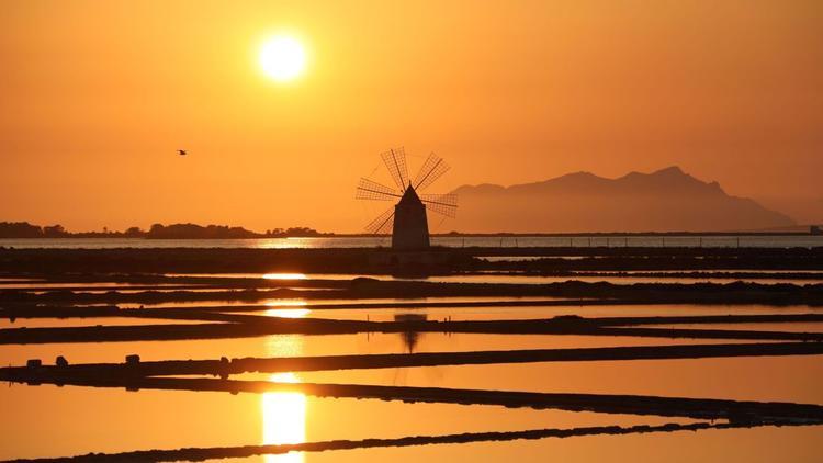 Marsala, Italy: Mặt trời lặn trên một cối xay gió ở thị trấn Marsala của bờ biển Sicily, nổi tiếng là xứ sở rượu vang.